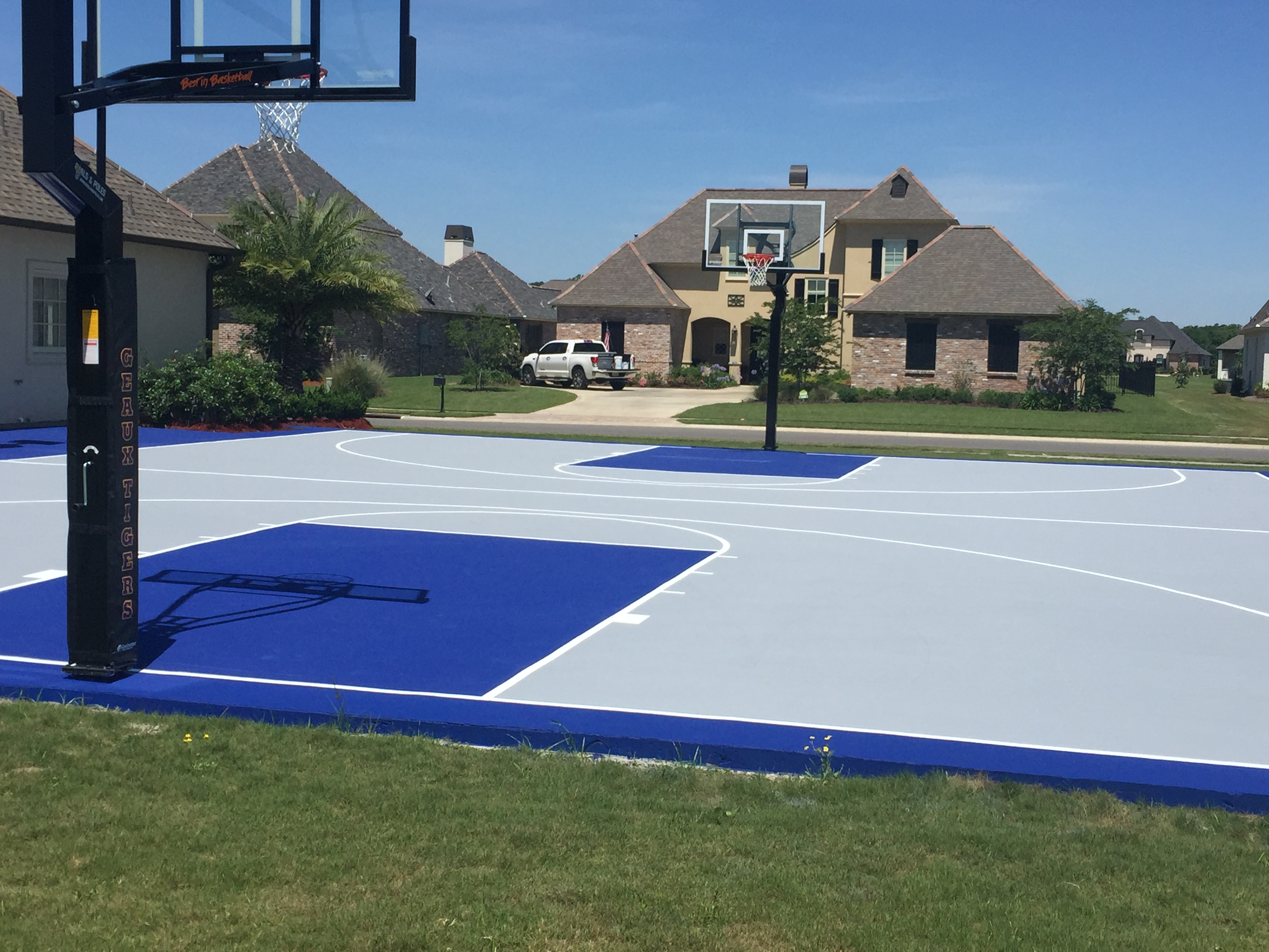 Full size basketball court with acrylic surfacing in bright blue and grey