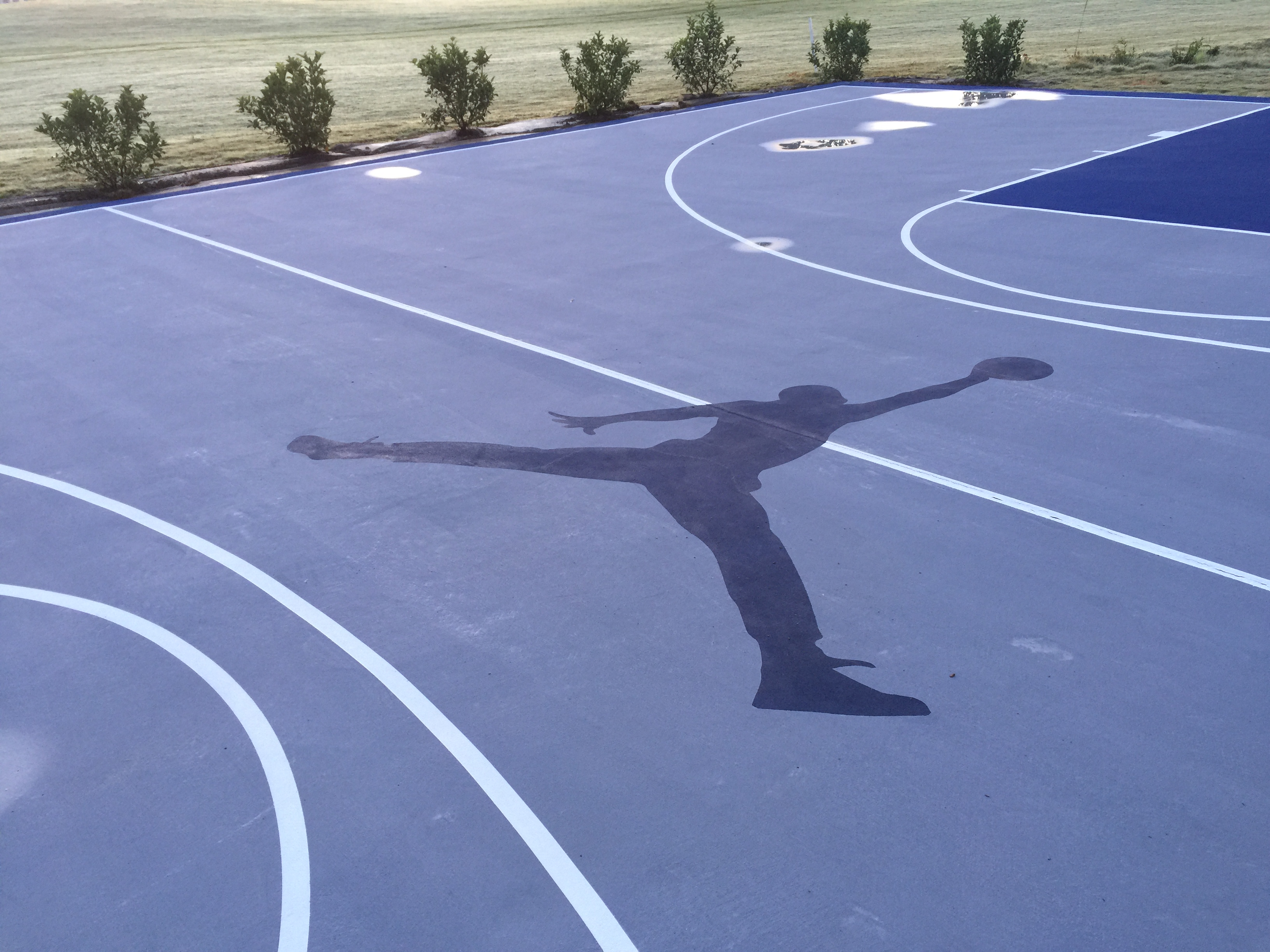 "Grey and blue court with ""jump man"" logo"